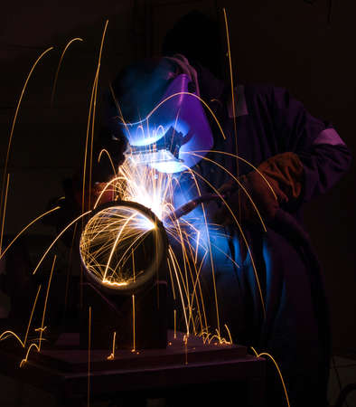 fabrication: Welder uses torch to make sparks during manufacture of metal cylinder. Stock Photo