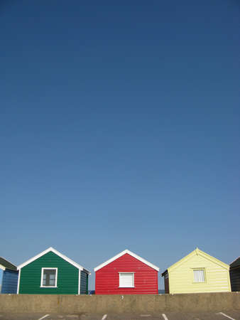 southwold: Green, red and yellow beach huts on sunny day in Southwold, Suffolk, England, UK Stock Photo