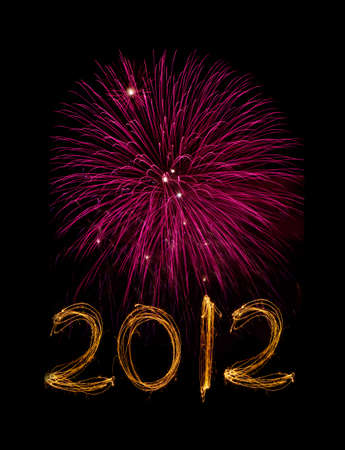 Celebration sparklers writing 2012 against black background with pink fireworks Standard-Bild