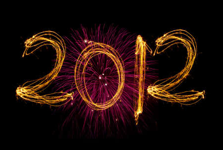 written date: Celebration sparklers writing 2012 against black background with pink fireworks Stock Photo
