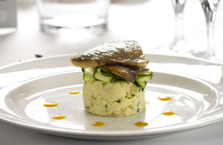 jus: Salmon dish with courgettes and jus on potatoes plated in gourmet restaurant