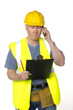 Construction worker on white background looks at clipboard and takes phone call