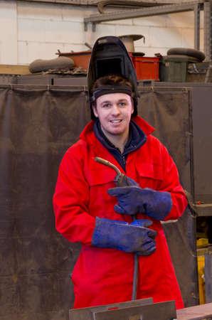 Soldador en la construcci�n de taller de fabricaci�n de metal mira a la c�mara, mientras que llevar la antorcha y vestidos con monos y las viseras de seguridad. Foto de archivo