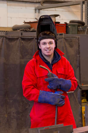 Welder in workshop manufacturing metal construction looks at camera whilst carrying torch and wearing overalls and safety visor.