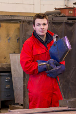 Welder in workshop manufacturing metal construction looks at camera and holds helmet and torch photo
