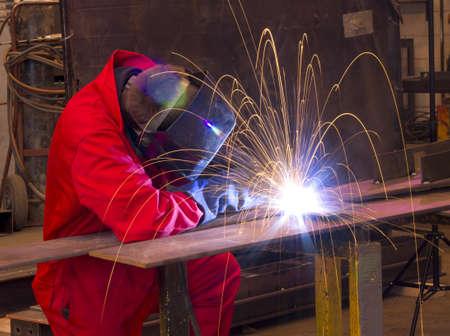 soldador: Soldador en la construcción de taller de fabricación de metal por el corte en cualquier forma con enormes chispas de color naranja