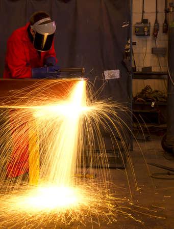 soldadura: Soldador en la construcción de taller de fabricación de metal por el corte en cualquier forma con enormes chispas de color naranja
