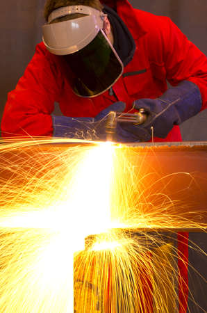Welder in workshop manufacturing metal construction by cutting to shape using huge orange sparks photo