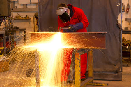 Welder in workshop manufacturing metal construction by cutting to shape using huge orange sparks Stock Photo - 12583710