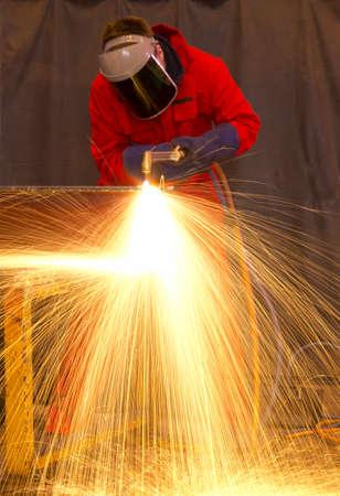Soldador en la construcci�n de taller de fabricaci�n de metal por el corte en cualquier forma con enormes chispas de color naranja