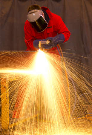 obscured face: Welder in workshop manufacturing metal construction by cutting to shape using huge orange sparks