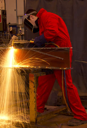 Welder in workshop manufacturing metal construction by cutting to shape. photo
