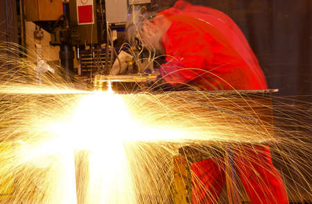 Blurred welder busy in workshop manufacturing metal construction  Many sparks shower from the torch  photo