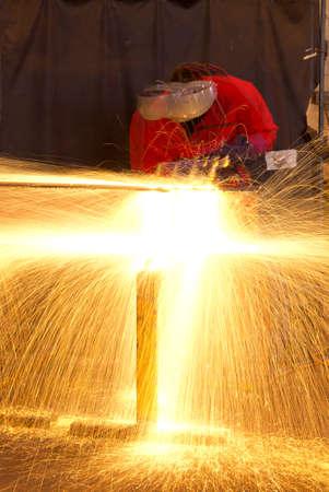 Exposici�n m�ltiple de soldador en la construcci�n de taller de fabricaci�n de metal por una ducha de chispas debido a la antorcha