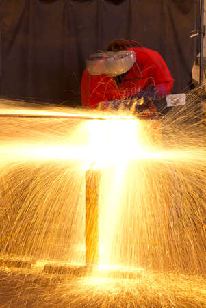 Multiple exposure of welder in workshop manufacturing metal construction by showering sparks from torch  Standard-Bild