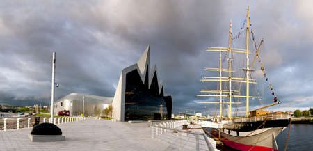High resolution panorama of the River Clyde in Glasgow featuring the Riverside Museum and Tall Ship  The sun is setting as storm clouds gather  Editorial