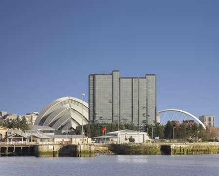 Blue sky and sunshine beside River Clyde in Glasgow showing landmark buildings Standard-Bild