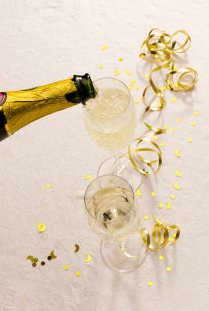 Champagne is poured from a bottle into two glasses beside golden table decorations