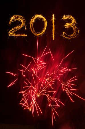 2013 escrito en sparklers aislados en negro con fuegos artificiales rojos reventar