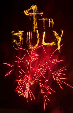 written date: Pink fireworks display with 4th July written in sparklers Stock Photo