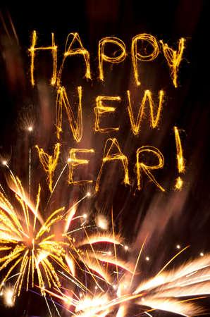 Sparklers deletrear Feliz A�o Nuevo encima de los fuegos artificiales de oro reventar