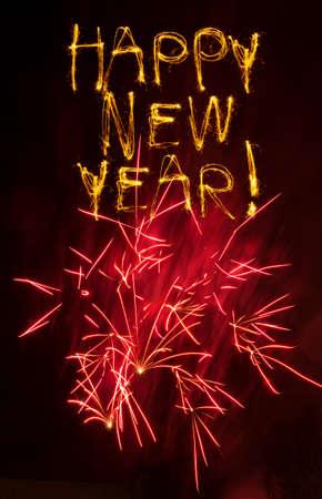 Sparklers escribir Feliz A�o Nuevo con fuegos artificiales rojos estallar abajo