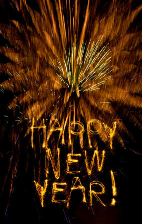written date: Sparklers write Happy New Year on golden fireworks burst