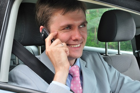 Businessman in car talking on mobile phone photo