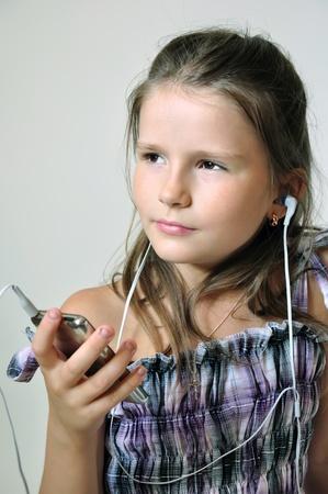 ヘッドフォンを通してキリスト教音楽を楽しんでいる子供。 写真素材