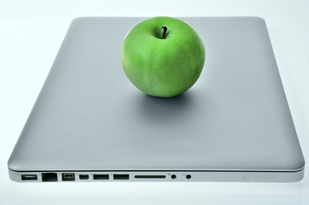Laptop with green apple on the cover. photo
