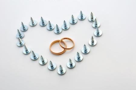 多くのハートの形のネジと、中心の結婚指輪。コンセプト - 夫婦困難、夫婦間の脆弱性、離婚、障害を克服する労働者の記念日。
