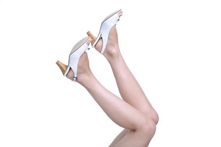 白い背景の上の高いヒールの靴で女性の足。