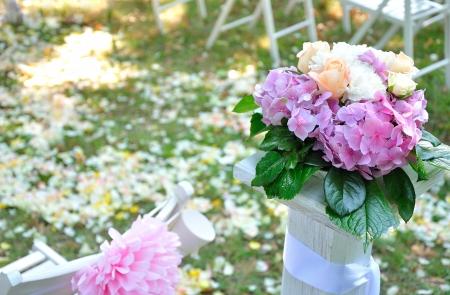 結婚式。緑の草や木製のスタンドに花の花びら。