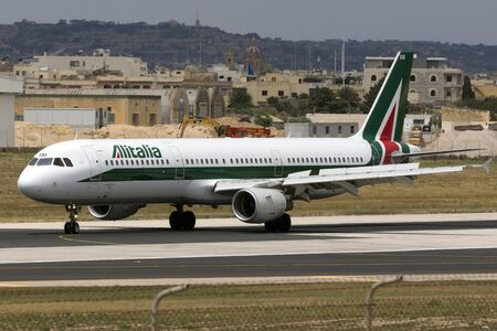 braking: Luqa, Malta - 2 July 2016: Alitalia Airbus A321-112 [I-BIXM] braking after landing runway 13, and entering apron 9 from taxiway Charlie.