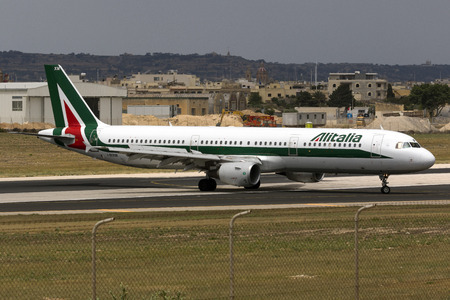 braking: Luqa, Malta - July 2, 2016: Alitalia Airbus A321-112 [I-BIXM] braking after landing runway 13, and entering apron 9 from taxiway Charlie.