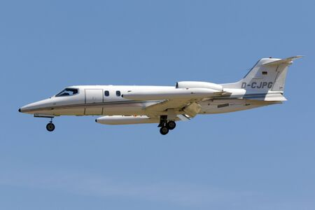 avionics: Luqa, Malta July 29, 2017: A private German registered Learjet 31A on final approach in the hot midday sun.