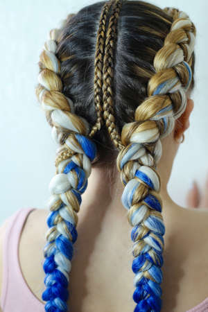 creative hairstyle of two braids with vpoyeniem blue kanekalona, Banco de Imagens