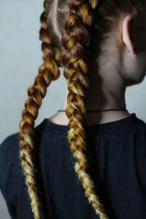 hairstyle of two braid with kanekalon on the hair of a red girl