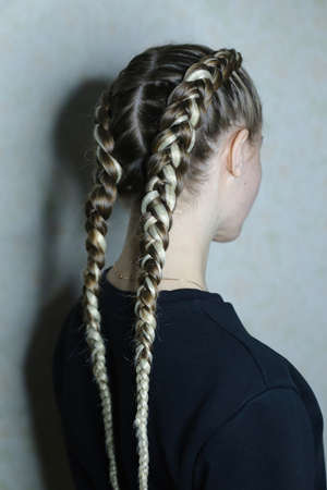 hairstyle of two braids with a kanecalon on the hair of a blond