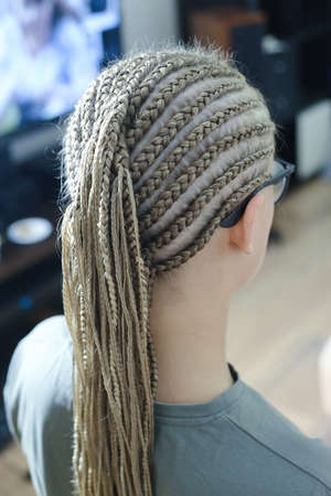 a lot of thin African plaits with artificial material, blond close-up on a light background, beauty studio 版權商用圖片