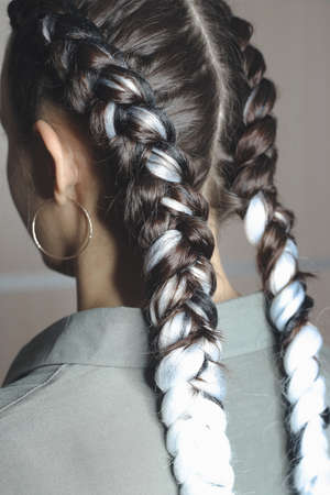 two large braids on the head of a girl, braided hair with artificial material kanekalon