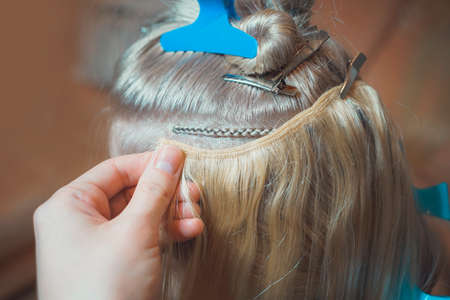 hair extension on tress in Hollywood way, African style, master in the process of work step by step