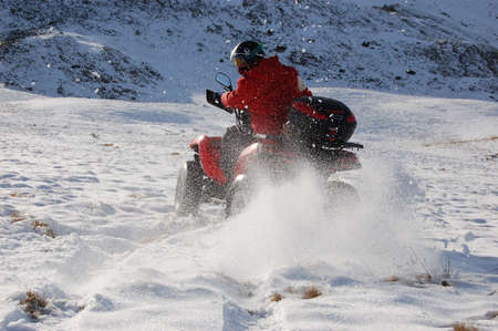 man riding quad in snow