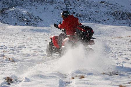 man riding quad in snow