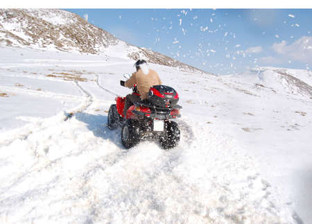 Man riding quad in mountain snow