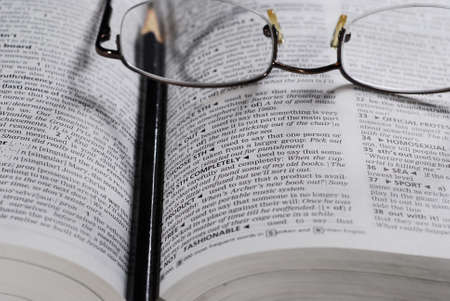 closeup of open book, reading glasses and pencil for notes