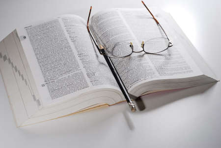 open book, reading glasses with pencil on a table