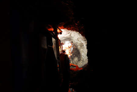 heavy duty mine machine working inside a dark mine shaft