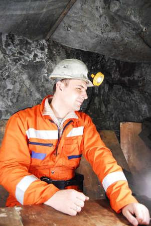 Miner in a mine shaft having break from work stock photo Standard-Bild