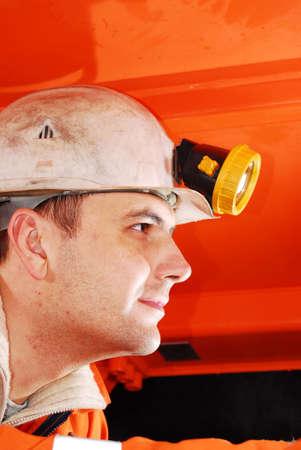 Miner operating a heavy duty machine in a mine shaft stock photo Standard-Bild